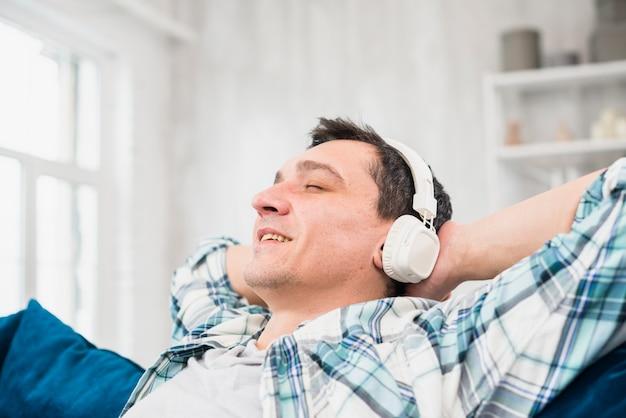 Homem alegre com os olhos fechados, ouvindo música em fones de ouvido no sofá