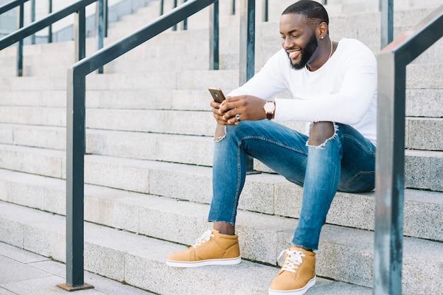 Homem alegre com smartphone nas escadas