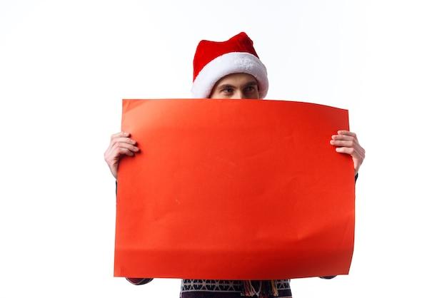 Homem alegre com um chapéu de natal e um pôster de mockup vermelho em estúdio.