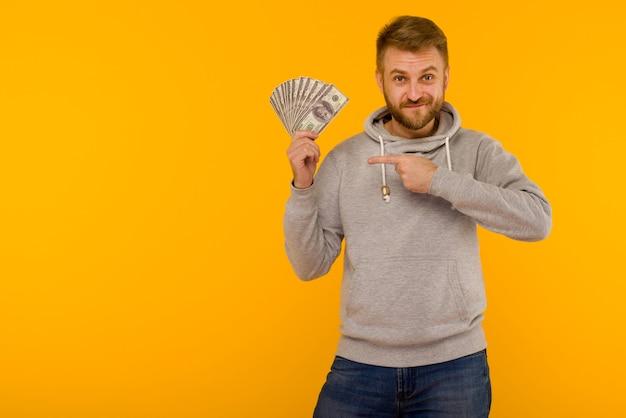 Homem alegre com um moletom cinza apontando o dedo para dólares em um fundo amarelo
