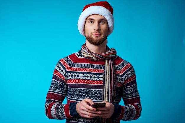 Homem alegre com um telefone na mão férias natal tecnologia fundo azul