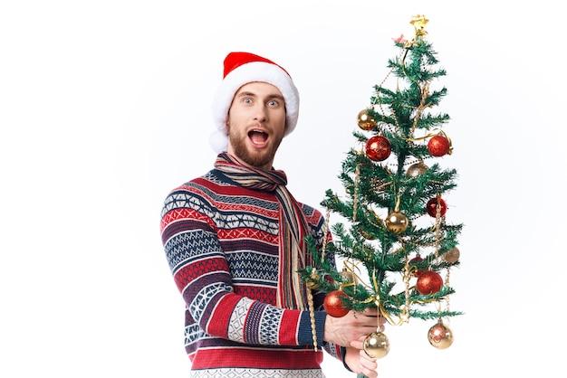 Homem alegre com uma árvore nas mãos, enfeites de fundo isolado de diversão de férias