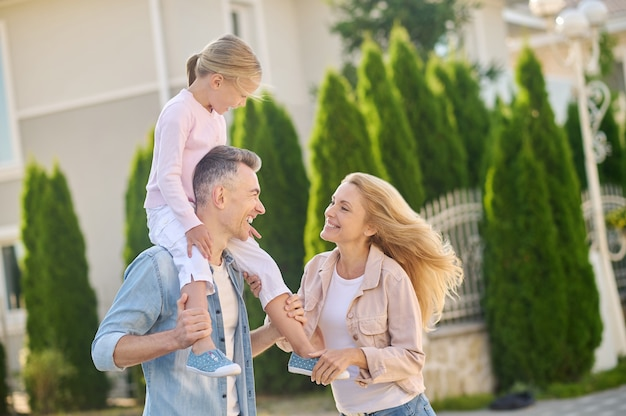 Homem alegre com uma garota nos ombros e uma mulher