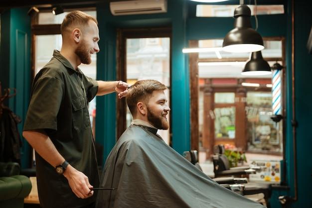 Homem alegre cortando cabelo de cabeleireiro com uma tesoura enquanto está sentado na cadeira.