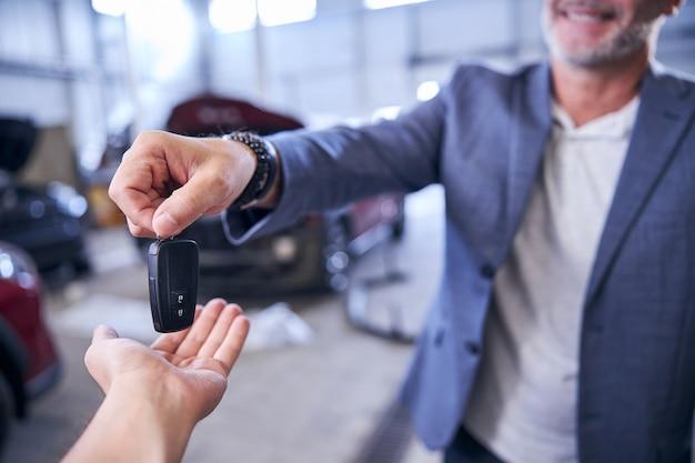 Homem alegre dando a chave do carro inteligente para o mecânico na estação de serviço
