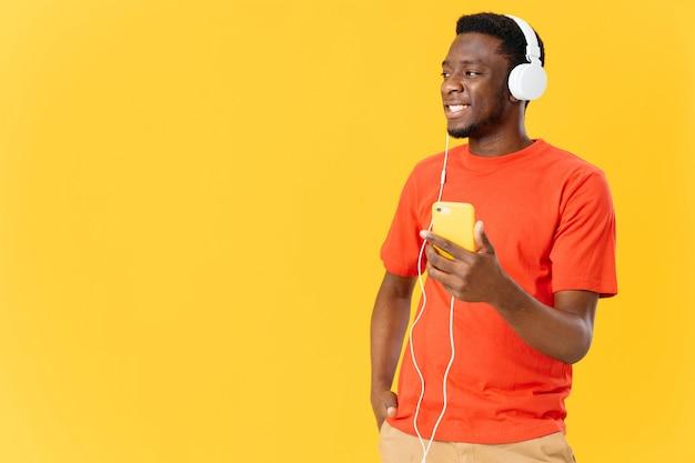 Homem alegre de aparência africana em fones de ouvido com um telefone ouve música de fundo amarelo
