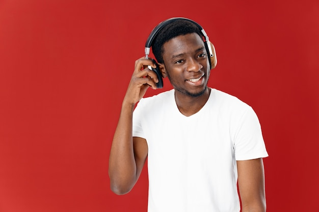 Homem alegre de aparência africana em fones de ouvido em fundo de estúdio isolado de camiseta branca