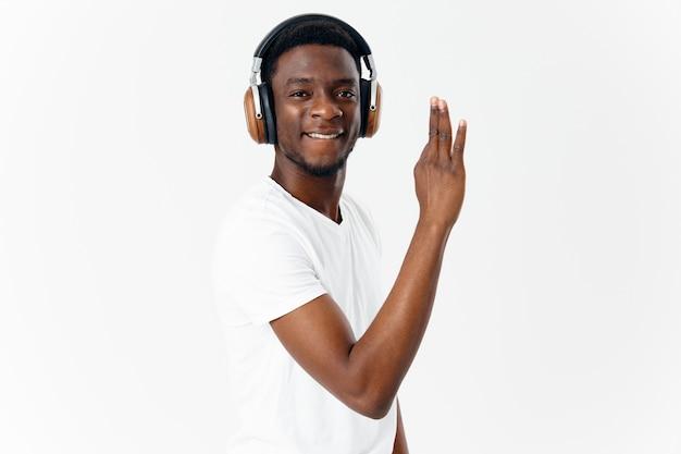 Homem alegre de aparência africana em fones de ouvido gesticulando com entretenimento musical de mão