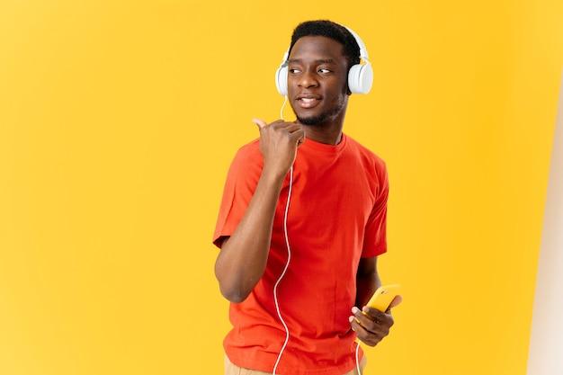 Homem alegre de aparência africana em fones de ouvido música fundo amarelo