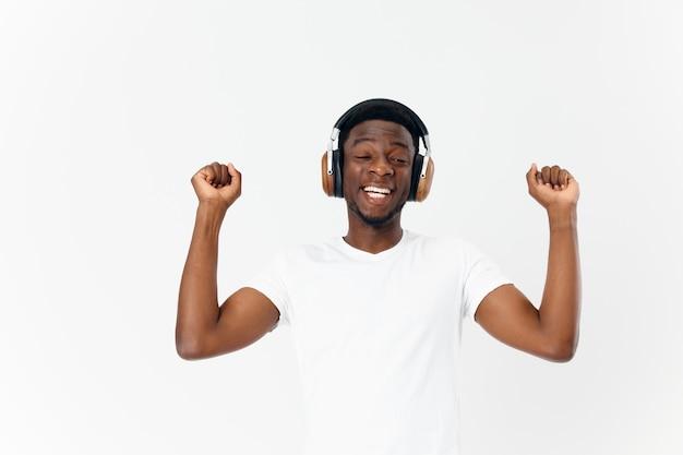 Homem alegre de aparência africana em fones de ouvido ouve estúdio de entretenimento musical
