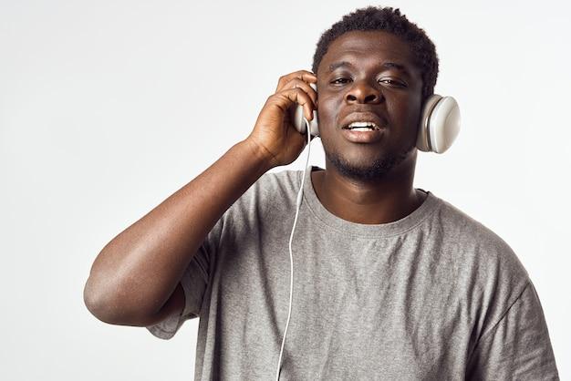 Homem alegre de aparência africana em fones de ouvido ouve música