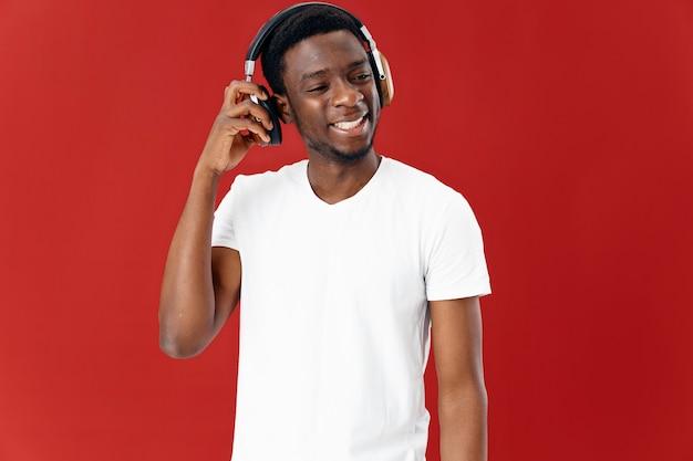 Homem alegre de aparência africana em fones de ouvido, ouvindo música, estilo de vida