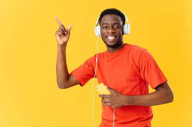 Homem alegre de aparência africana em tecnologia de música de fones de ouvido. foto de alta qualidade