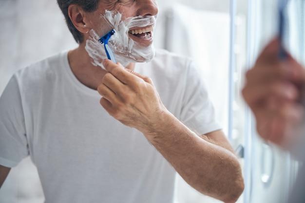 Homem alegre de cabelos curtos, barbeando o rosto com uma navalha