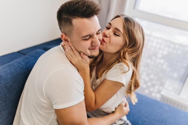 Homem alegre de cabelos escuros em traje branco, passando a manhã com a esposa. adorável loira beijando o namorado no fim de semana.