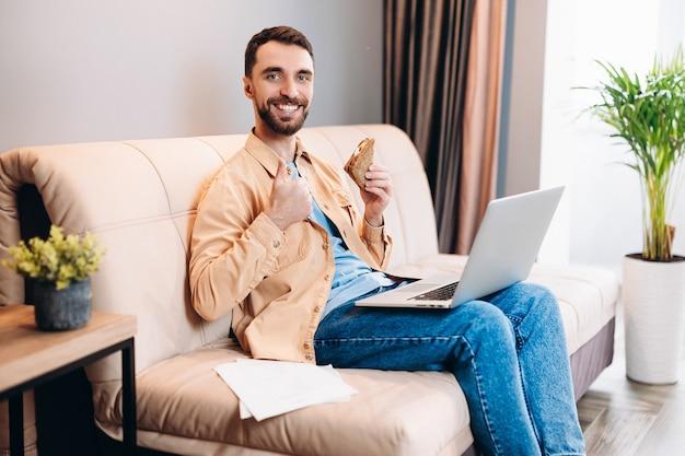 Homem alegre de camisa laranja e calça jeans azul faz gesto de polegar para cima e segura o sanduíche em outro
