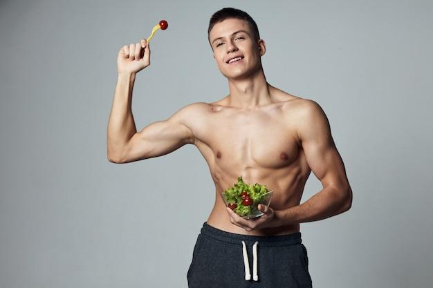Homem alegre de esportes com prato de salada, energia, dieta, comida, isolado, fundo