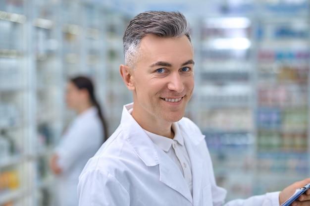 Homem alegre de jaleco branco na farmácia