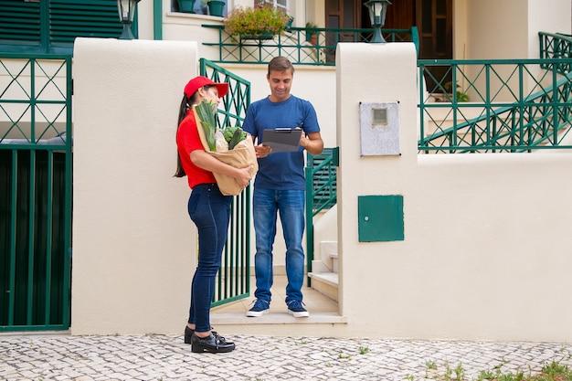 Homem alegre de meia-idade, assinando para receber pedidos do supermercado, em pé e sorrindo. entregadora de uniforme vermelho, segurando o saco de papel com legumes. serviço de entrega de comida e pós-conceito