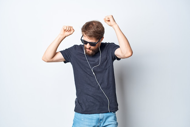 Homem alegre de óculos, ouvindo música com fones de ouvido, estilo de vida de estúdio