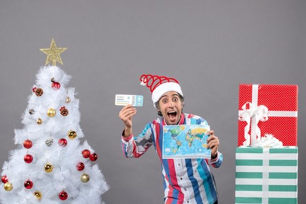 Homem alegre de vista frontal com chapéu de papai noel com mola em espiral segurando um mapa-múndi e um bilhete de viagem