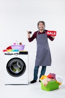 Homem alegre de vista frontal segurando um cartão e uma placa de venda em pé perto da máquina de lavar no fundo branco