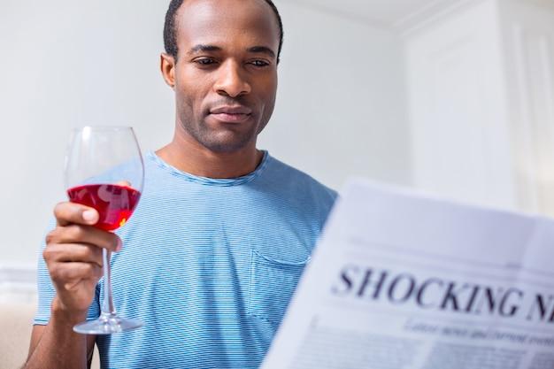 Homem alegre e agradável sentado em casa tomando vinho enquanto lê artigos