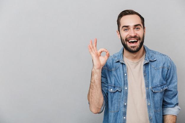 Homem alegre e animado vestindo camisa isolada sobre parede cinza, mostrando ok