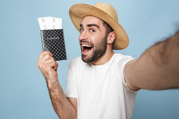 Homem alegre e animado vestindo camiseta em branco, isolado na parede azul, tirando uma selfie, mostrando passaporte com passagens aéreas