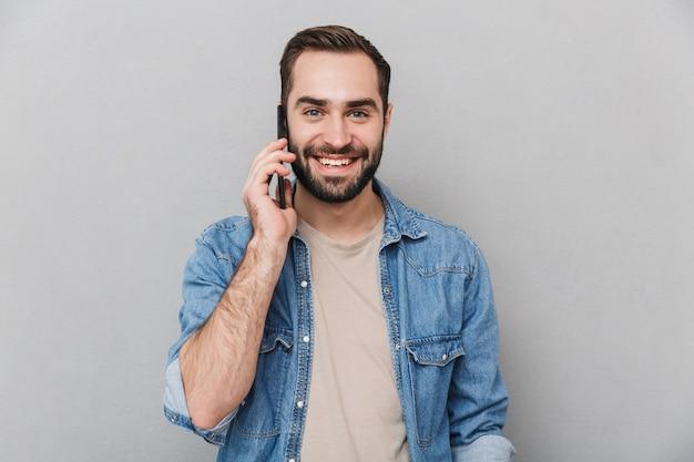 Homem alegre e animado vestindo uma camisa isolada sobre uma parede cinza, falando no celular