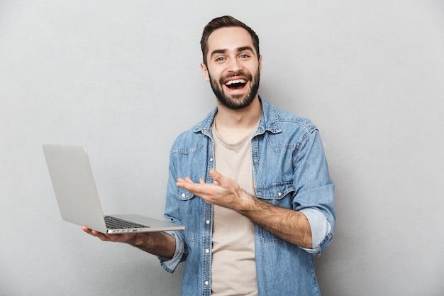 Homem alegre e animado vestindo uma camisa isolada sobre uma parede cinza, mostrando um laptop