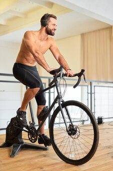 Homem alegre e atlético andando de bicicleta e ouvindo música