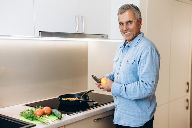 Homem alegre e bonito com cabelo grisalho corta pimentas para adicionar ao seu prato vegetariano