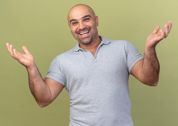 Homem alegre e casual de meia-idade mostrando as mãos vazias isoladas na parede verde oliva