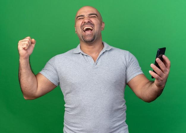 Homem alegre e casual de meia-idade segurando um celular, fazendo um gesto de sim com os olhos fechados, isolado na parede verde