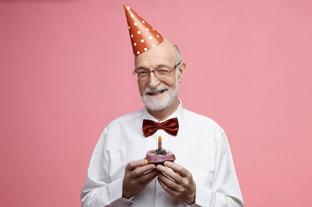 Homem alegre e elegante de barba na casa dos 80 anos usando chapéu de festa de cone vermelho, segurando um pedaço de bolo de chocolate delicioso com uma vela, fazendo pedido, piscando, em clima de festa