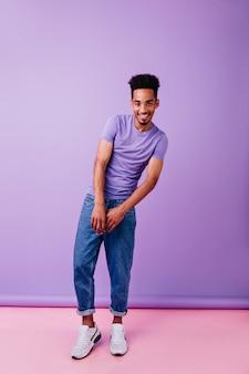 Homem alegre e emocional com aparência engraçada de penteado. negro interessado em uma camiseta roxa posando com um sorriso tímido