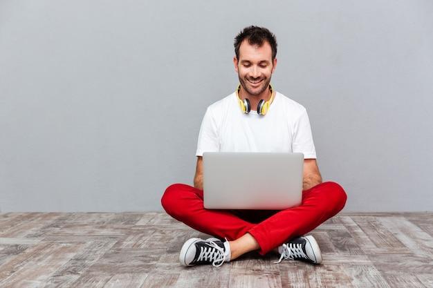 Homem alegre e feliz casual usando laptop enquanto está sentado no chão sobre um fundo cinza