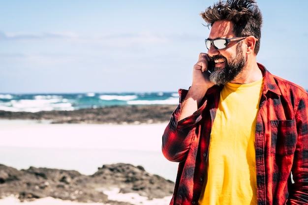 Homem alegre e feliz hippie com barba e óculos escuros falando ao telefone com amigos em atividades de lazer ao ar livre em beuaitufl lugar