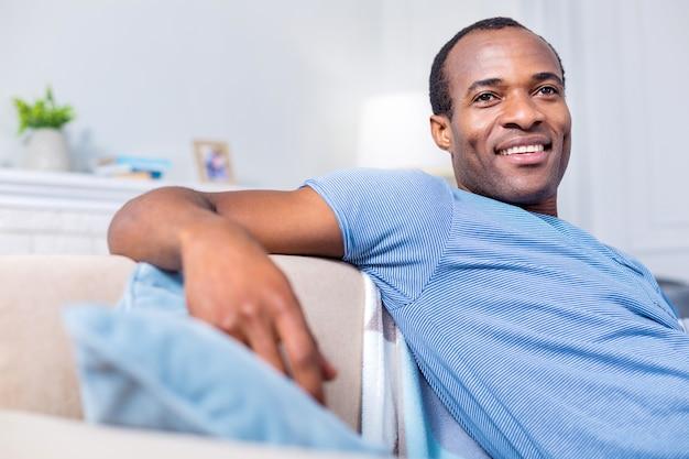 Homem alegre e feliz sorrindo e se sentindo feliz enquanto desfruta de seu tempo em casa