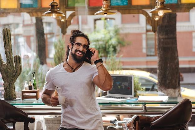 Homem alegre e feliz tomando um expresso enquanto fala ao telefone