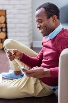 Homem alegre e inteligente olhando para os números do cartão de crédito e sorrindo enquanto faz transações de dinheiro