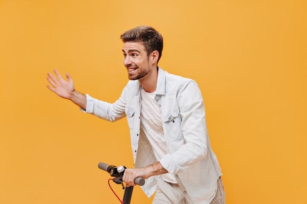 Homem alegre e moderno com barba ruiva em uma camiseta clara e jaqueta jeans sorrindo, olhando para longe e posando com scooter na parede laranja