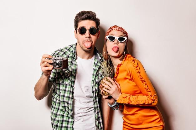 Homem alegre e mulher de óculos escuros estão mostrando línguas e posando com a câmera retro e abacaxi no espaço isolado.