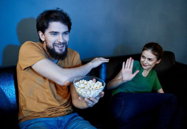 Homem alegre e mulher emocional em um sofá preto dentro de casa à noite assistindo tv