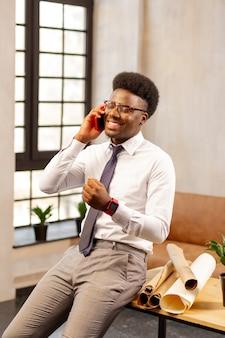 Homem alegre e positivo falando com seu cliente enquanto faz uma ligação