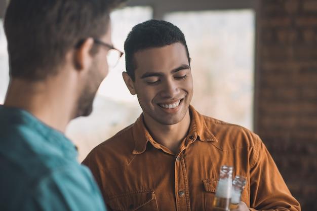 Homem alegre e positivo sorrindo enquanto bebe cerveja com o amigo