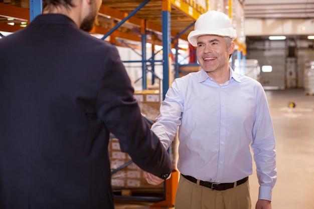 Homem alegre e positivo sorrindo enquanto cumprimenta seu chefe no armazém
