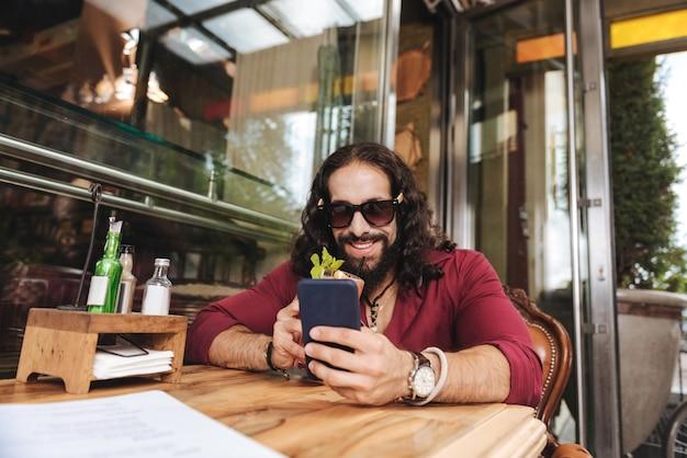 Homem alegre e positivo sorrindo enquanto usa seu dispositivo móvel