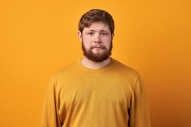 Homem alegre e satisfeito com a barba por fazer faz um quadro com as duas mãos e se prepara para ser fotografado